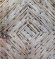 The door of the old country house is made of diagonal planks and rusty nails