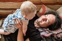 Playful man lying on couch playing with son