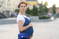 Pregnant Adult Woman In Blue Clothes Walks Outdoor