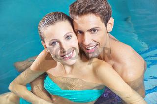 Paar sitzt zusammen im Wasser vom Pool