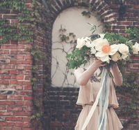 Woman in boho dress holding lush bouquet