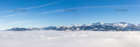 Fantastic panoramic view of snow mountain range stick out of inversion fog layer. Great panorama with sunny blue sky above the clouds. Ofterschwanger Horn, Alps, Allgau, Bavaria, Germany.