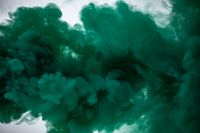 Green smoke bomb exploding against white background