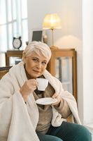 Cheerful Senior Woman Wrapped In A Warm Knitted Plaid Relaxing At Home