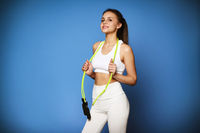 Confident sportswoman with skipping rope