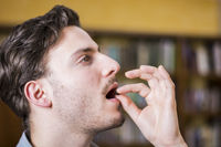 Man at home taking medicine tablet or pill