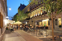 Night city street with bicycles. City bike rental at night