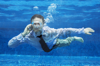Caucasian businessman talking on a mobile phone underwater