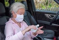 Seniorin mit Mundschutz desinfiziert sich die Hände im Auto