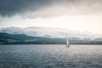 Sailing boat floats on the lake with stormy clouds sky. Autumn sailboat ship water sport scene from Lipno, Czech republic, Sumava.