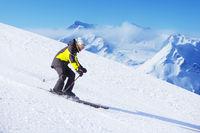 Alpine skier on piste ride downhill
