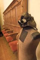 Alte Schneiderpuppe mit Lederhelm und Brille steht vor leeren Kirchenbänken