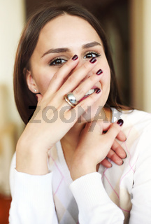 Cheerful young woman covering face while smiling