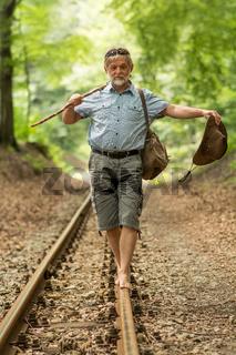 Rentner wandert mit Stock und Hut auf Gleise
