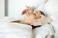 Crop massage therapist massaging face of client
