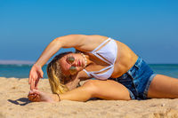 Young dutch woman bending sideways on beach