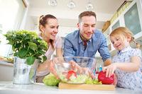 Familie bereitet zusammen gemischten Salat vor