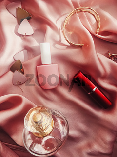 Fashionable and stylish accessories, jewelry and make-up products on pink silk background, beauty and fashion