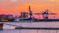 Cranes unload cargo in a seaport during sunset