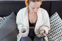 Stay at home. Social distancing. Woman at home relaxing on sofa couch drinking tea from white cup, listening to relaxing music, stay connected to friens and family via social networks on mobile.