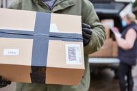 Paket Lieferung wird von Paketboten gehalten