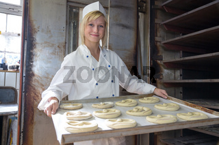 Baker putting pretzels into oven in a bakery