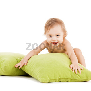cute little boy playing with green pillows