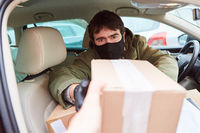 Paketbote im Auto gibt Paket bei Lieferung ab