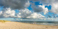 Beach sand panorama with people and dogs. Blue sky and dramatic clouds at coastline waterfront in soft evening sunset light. Hvidbjerg Strand, Blavand, North Sea, Denmark.