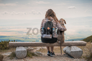 Young attractive woman with her dog enjoying the view from a bench in the mountains. Vacation with pets concept. Dog is sitting next to her.