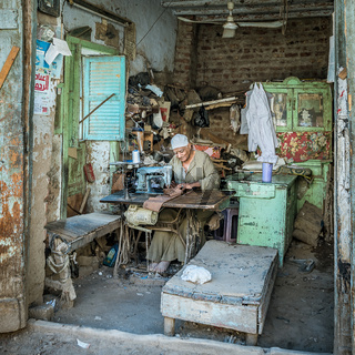 A poor egyptian tailor sewing in his shed