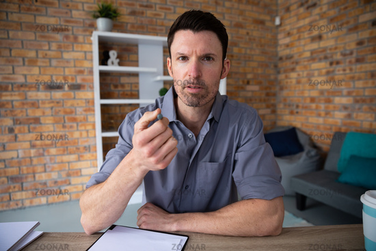 Portrait of man making hand gestures while sitting on his desk
