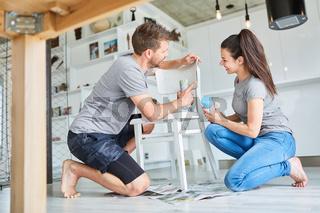 DIY Paar beim Streichen und Lackieren von Stuhl