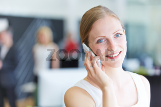 Frau telefoniert mit Smartphone im Büro
