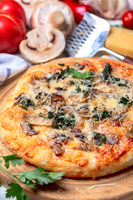 Homemade pizza with mozzarella, mushrooms and spinach.