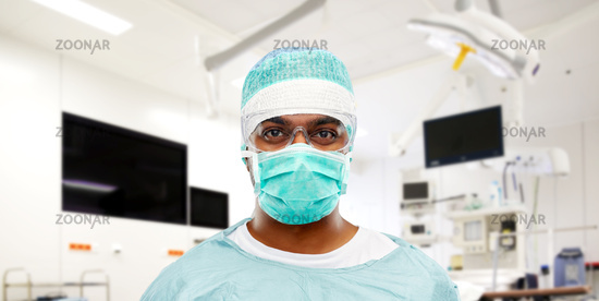 indian male surgeon in mask over operating room
