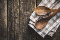 Two wooden spoons on checkered napkin on old wooden table.