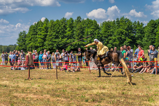 Warrior throwing javelin at dummy, horseback riding show
