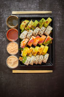 Asian food delivery home, various sushi sets in plastic containers with sauces, rice and chopsticks