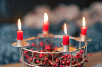 Red candles burning on selfmade Advent wreath made of wire grid decorated with red dried berries with blurred couch living room in background