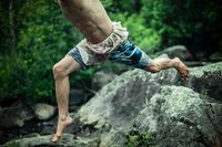 Athletic man rock jumping in nature