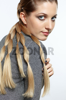 Portrait of blonde female with creative braid hairdo.