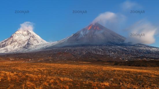 Autumn mountain landscape view at sunrise of eruption active volcano