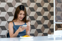 asian influencer food blogger take photo in new normal restaurant