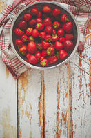 Freshly harvested strawberries. Metal colander filled with juicy fresh ripe strawberries on an table