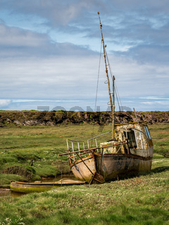 A damaged Boat in the grass, seen in Askam-in-Furness, Cumbria, England