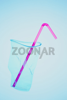 Squashed plastic cup and drink straw over blue background