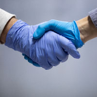 Handshaking with blue protective gloves