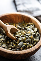 Peeled pumpkin seeds in wooden bowl and scoop.
