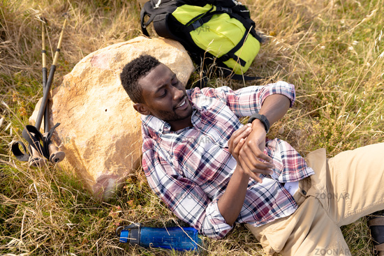 Fit african american man resting checking smartwatch and lying in mountain countryside